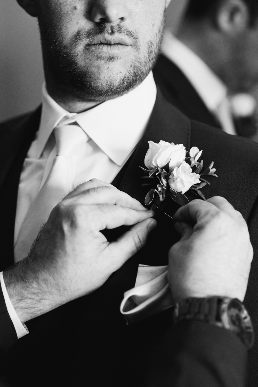 Groom puts on buttonhole flower