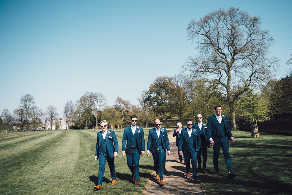 Groomsmen walk towards the pub before the wedding