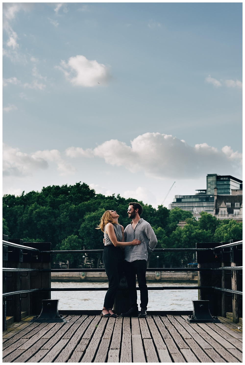 Couple laugh by the river Thames on their engagement shoot