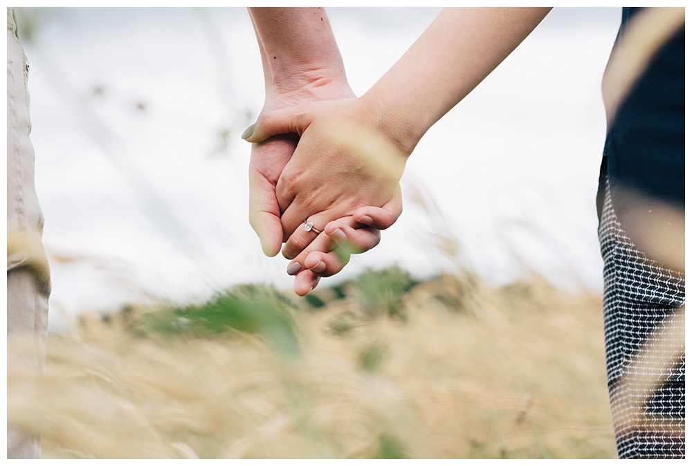 Couple hold hands in meadow with engagement ring