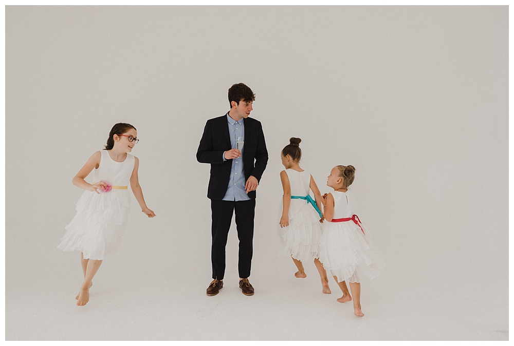 Groom surrounded by flower girls