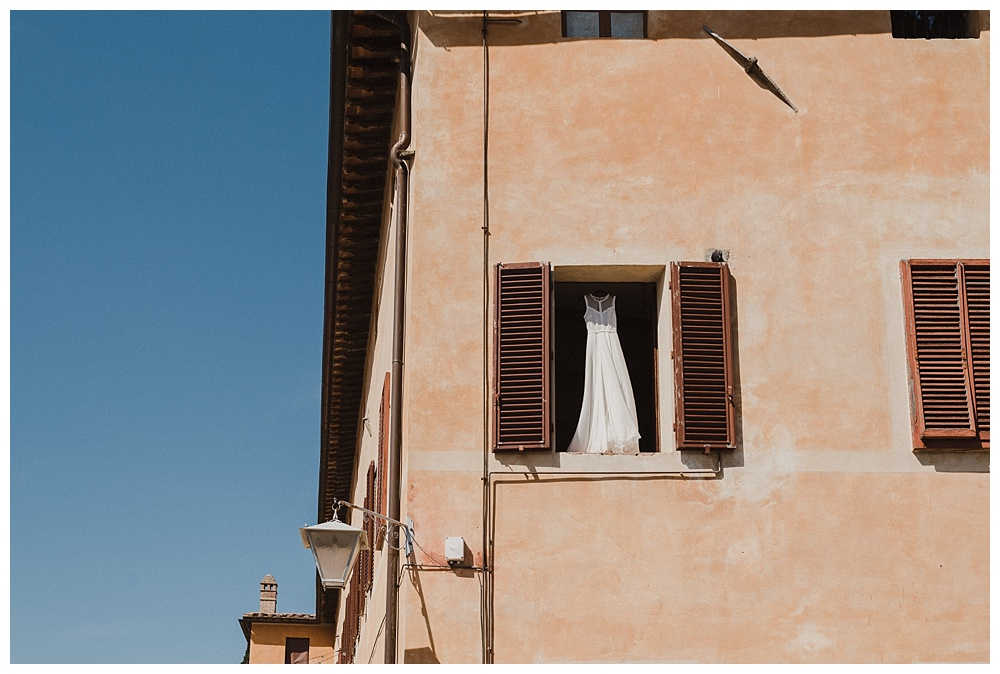 Wedding dress hanging in window of Villa Catignano