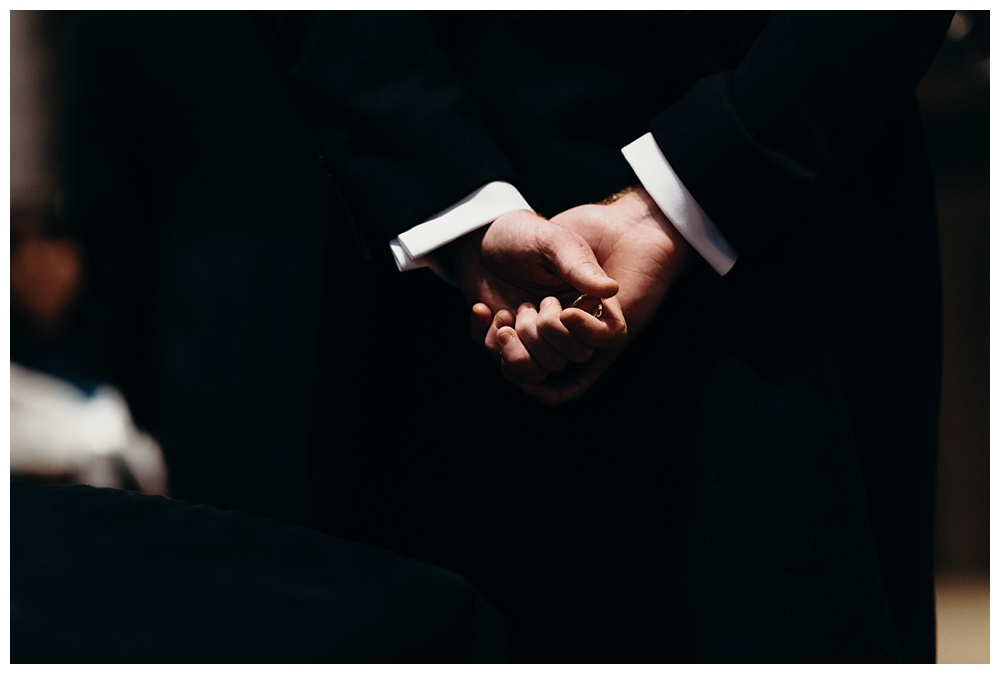 Best man holds ring during wedding ceremony.