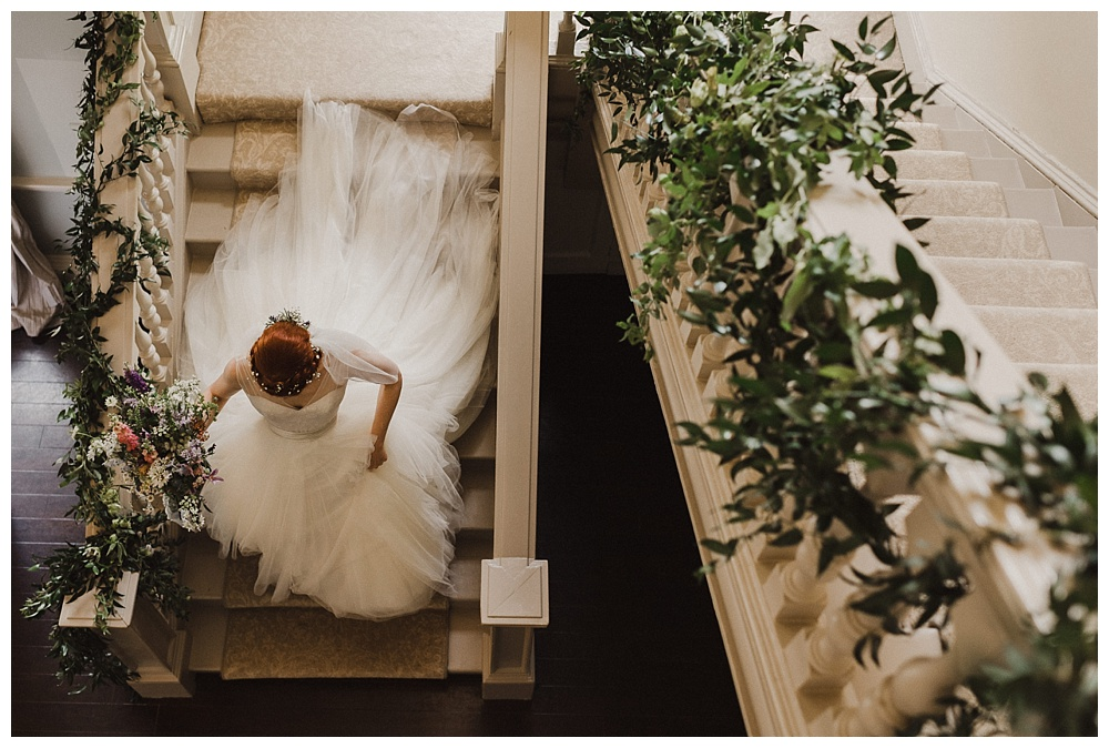 Bride sweeping down stairacse at Morden Hall