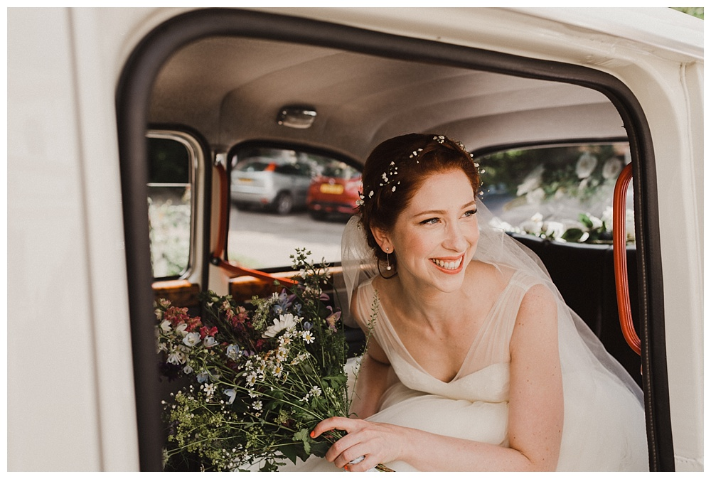Smiling bride in white London taxi cab Will Patrick Wedding Photography