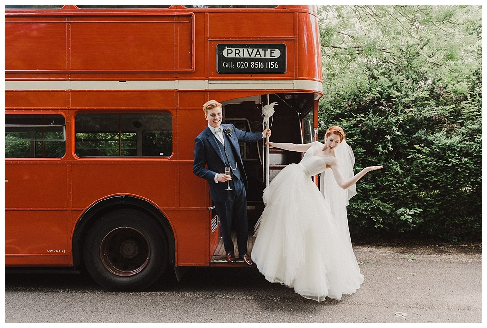Brdei and groom with old london bus wedding transport